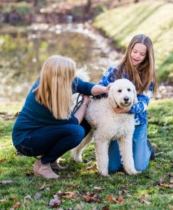 A therapist and her teen client  petting a dog during an outdoor session