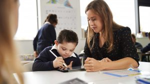 A woman watching her son draw a picture on a tablet