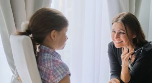 A therapist smiles while listening to a young girl speak