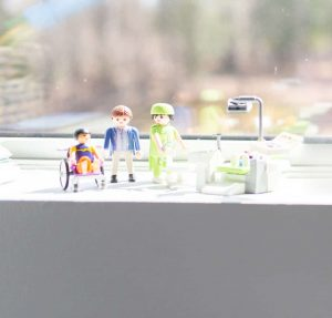 A series of children's toys sitting on a window sill