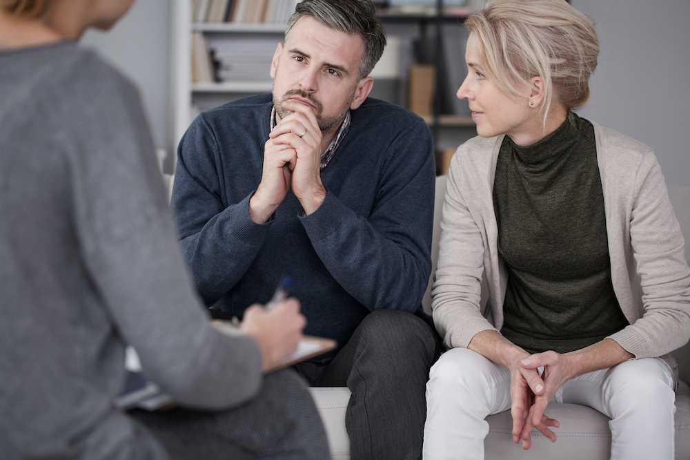 Wife Supporting Her Husband In Therapy With The Man Listening