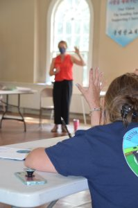 A teen girl raising her hand in a workshop led by Samantha Straub