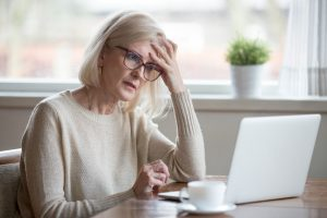 Thoughtful confused mature woman looking at laptop, suffering from memory loss