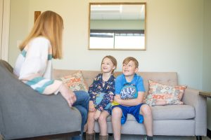 Siblings in a family therapy session with female therapist